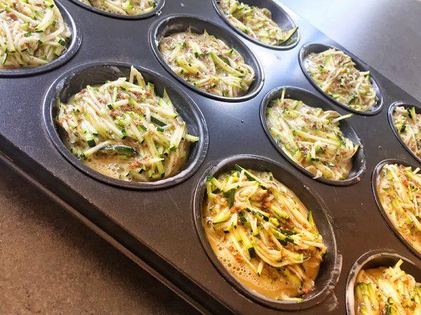 Die Zucchini waschen und den Blütenansatz entfernen. Mit einem Juliennehobel in feine Juliennestreifen hobeln oder mit einer Reibe fein raspeln. Mit den Eiern, dem geschroteten Leinsamen und den Gewürzen vermischen und in die vorbereiteten Muffinmulden einfüllen.