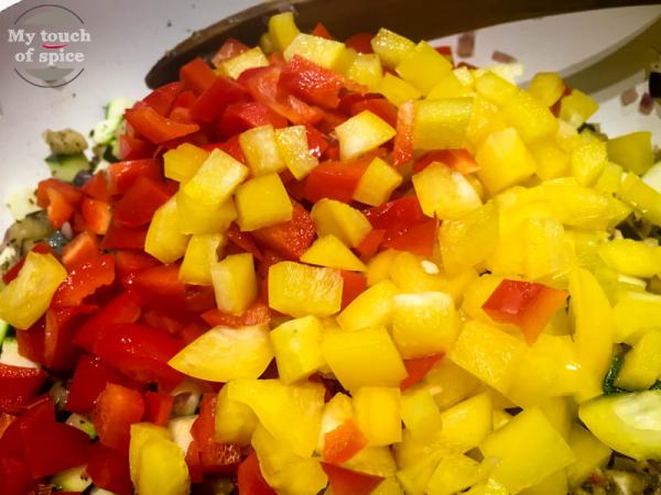 Als letztes die Paprika und Tomaten (Dosentomaten) zugeben und mit der Gemüsebrühe aufgiesen. Die Kräutern der Provence unterrühren. Bei milder Hitze abgedeckt ca. 10 Minuten schmoren lassen.